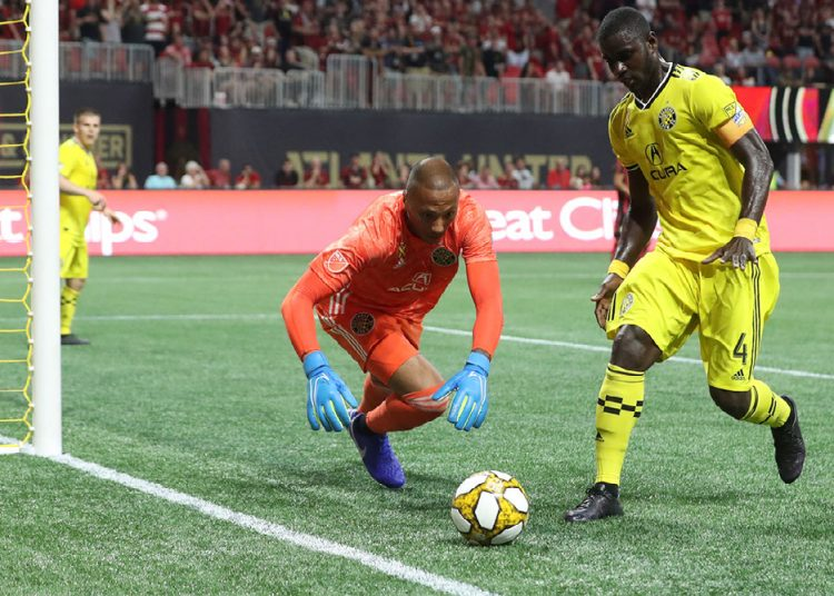 Sep 14, 2019; Atlanta, GA, USA; Columbus Crew goalkeeper Eloy Room (1) makes a save on a ball next to defender Jonathan Mensah (4) in the first half against the Atlanta United at Mercedes-Benz Stadium. Mandatory Credit: Jason Getz-USA TODAY Sports