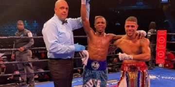 Duke Micah (middle) being adjudged winner of the bout by the referee (left) after the fight
