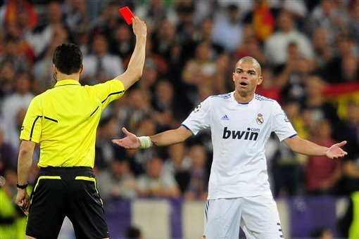 Real Madrid's Pepe from Portugal is shown a red card by the referee during their semifinal first leg Champions League soccer match against FC Barcelona at the Bernabeu stadium in Madrid, Spain, Wednesday, April 27, 2011. (AP Photo/Manu Fernandez)