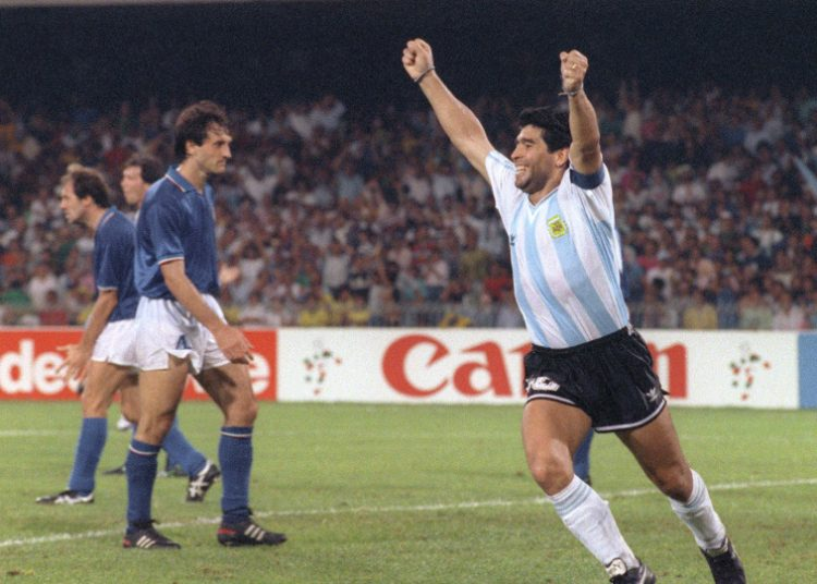 (FILES) In this file photo taken on July 03, 1990 Argentinian forward Diego Maradona (R) celebrates after teammate Claudio Caniggia (not pictured) tied the score at 1 during the World Cup semifinal soccer match between Italy and Argentina in Naples. - Argentinian football legend Diego Maradona passed away on November 25, 2020. (Photo by DANIEL GARCIA / AFP)